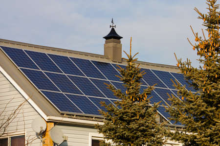 panel: A residential rooftop is shown covered with solar panels facing uo to the sky, leaving copy space Stock Photo