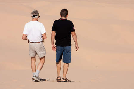 Two men engaged in conversation as they walk away from the camera into the sandy desert dunes background photo