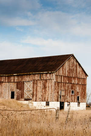 An old weathered bank barn with fields in the foreground A blue sky provides space for copy photo