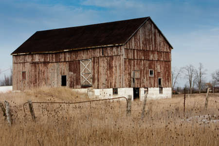 An old weathered bank barn with fields in the foreground photo