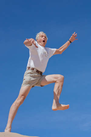 A mature male in his 60s takes a fearful leap into the blue yonder photo