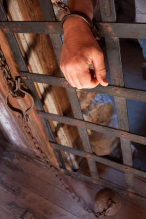 a mans hand is shackled to a vintage prison cell door with a ball and chain in view photo