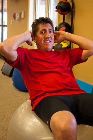 sit: A Man in his forties works out in the Gym doing sit ups on a yoga ball Stock Photo