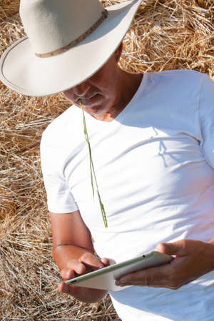 A cowboy leaning on a haystack using a tablet computer photo