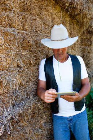 cowboy  farmer leaning on a haystack using a tablet computer Standard-Bild