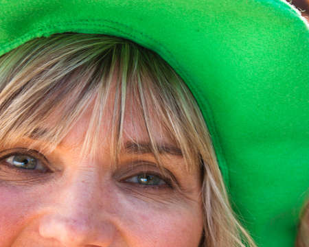 paddys: Close up partial face of a blonde woman with smiling blue eyes in a wide brimmed green hat
