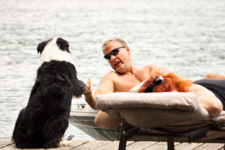 A sunbathing boater shakes the paw of a dog that has come to greet him on the dock  photo