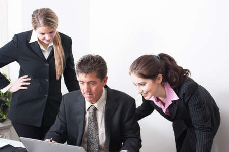 Three office workers gather around the computer in a discussion. Stock Photo - 18181270