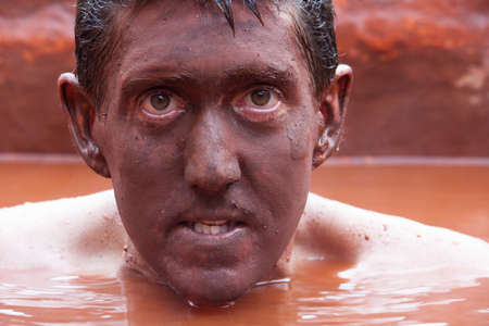 Close up of a man submerged in the red mud bath with his face completely covered in mud.