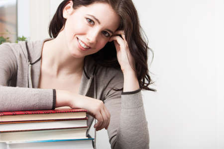 A beautiful college girl leans on a stack of books photo