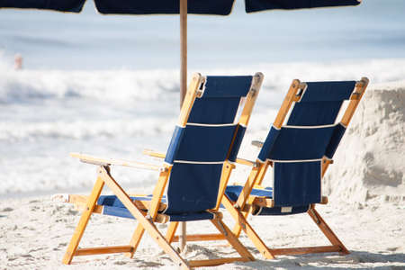 two luxury beach chairs sit under an umbrella on the sunny beach photo