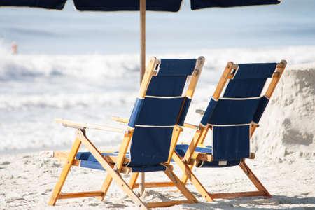 myrtle beach: two luxury beach chairs sit under an umbrella on the sunny beach