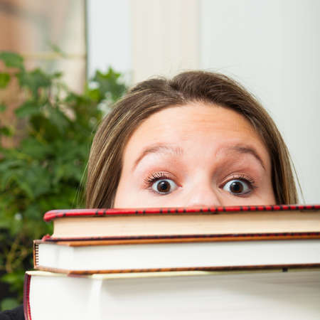 a female student behind in her reading peeks from behind her stack of books with a look of panic