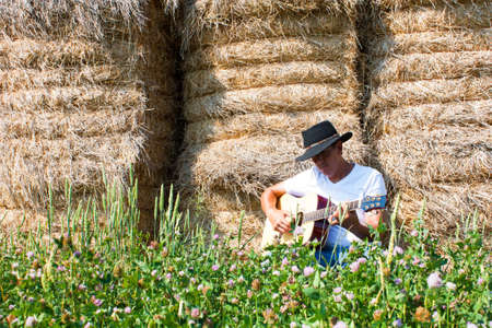 A cowboy sits in front of a wall of hay bales playing a gutar with summer field flowers in the foreground