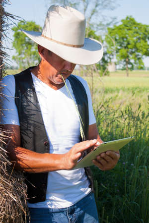 A cowboy leaning on the hay stack in a countryside setting using touchscreen on a tablet computer Stock Photo - 18495637
