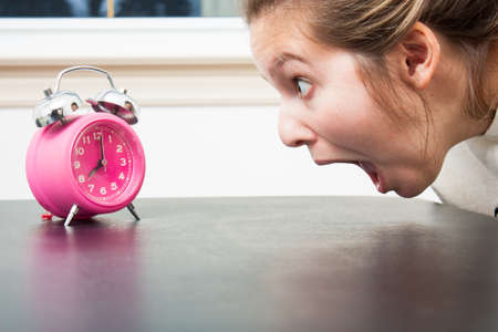 Close up as a young woman gapes at a pink alam clock in shocked panic