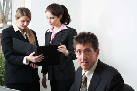 A professional man in a business man sits at a desk looking at the camera, while 2 female co-workers stand behind having a discussion over a portfolio photo