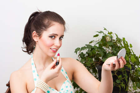 sidelong: A lovely young brunette in vintage dress looks sidelong at the camera while applying lipstick using a compact