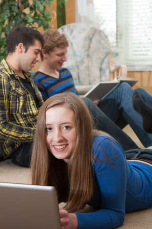 Teenage girl laying on floor using computer with two students in background studying  from a textbook Stock Photo - 18691534
