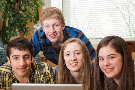 A diverse group of teenagers gathered around a laptop in a home setting looking at the camera