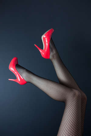 A pair of shapely female legs in fishnet stockings with shiny red high heeled shoes on a dark background