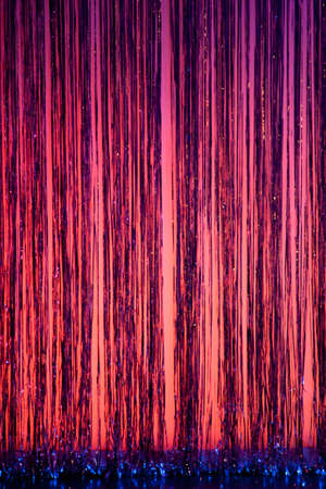 A stage curtain of pink purple and blue with streamers provides a colorful backdrop