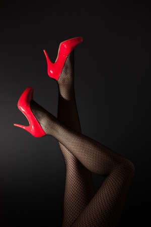 A pair of sexy legs in red high heels kicked into the air on black background Stock Photo
