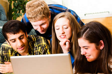 a group of teens viewing a computer screen together  High saturation