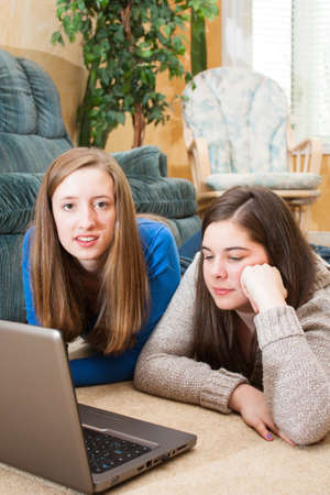 two teenage girls hanging out after school using a laptop Stock Photo - 19293130