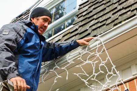 A man on a ladder putting up Christmas lights on the house Standard-Bild