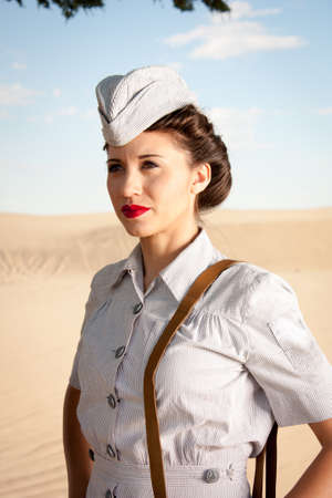 world war one: A beautiful young WWII nurse, in authentic uniform, stares off into the dry dusty landscape  close up head and shoulders  Stock Photo