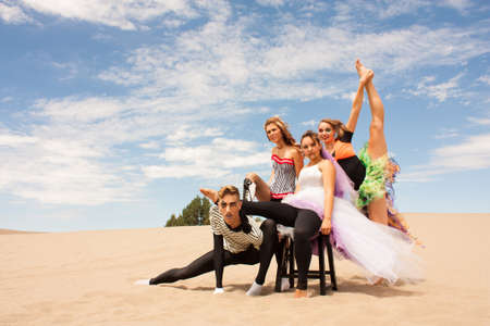 A young circus troupe balance, supporting each other on the desert sand photo