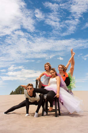 A young circus troupe pose supporting one another in the desert sand photo