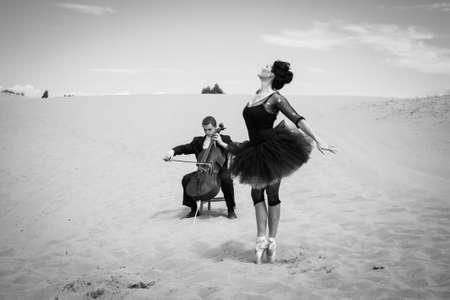 en pointe: A solo cellist plays for an elegant ballerina dancing in the barren desert  Stock Photo