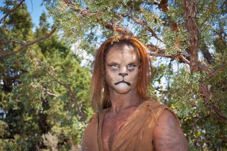 A Wild Lion man stares cautiously at the camera with a background of forest   This is the fantastic make-up done by Rayce Bird