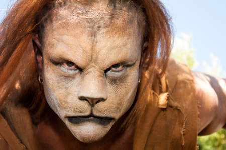 stage costume: Close -up and meancing face of a Lion man looking into the camera   Fantastic special FX make up of Rayce Bird