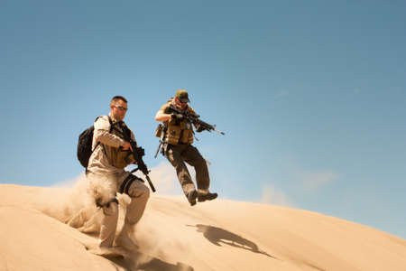 heavily: Two heavily armed Special forces officers jump over the bank in pursuit