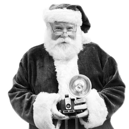 Een authentieke Kerstman heeft een oude vintage camera in zwart en wit