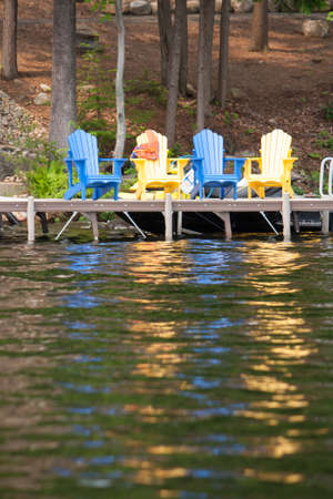 muskoka: Colourful Muskoka chairs sit on the cottage dock with a life jacket slung over one waiting for action Stock Photo