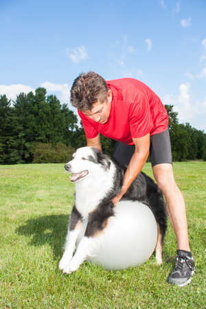 promotes: Dog trainer helping his dog stretch out his joints on a yoga ball.  Promotes good balance and health for dogs