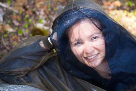 A Young woman camping in Northern Ontario in May wears bug protection gear to avoid mosquitoes that can carry West Nile Virus photo