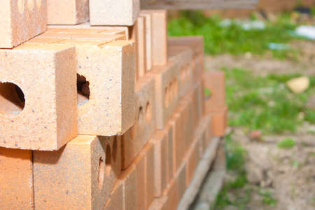 A pile of bricks sits on a skid at a school construction site waiting to complete the project Stock Photo
