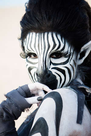 striking black and white zebra woman looks demurely over her shoulder   Stock Photo