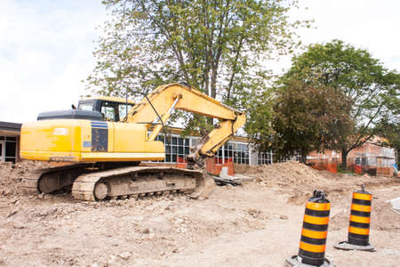 A local school site under renovation.  An excavator clears the area in the front with the school building in the background