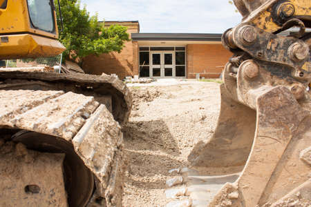 An ecxavating machine on a local elementary school renovation site, with the entrance doors in the background Stock Photo