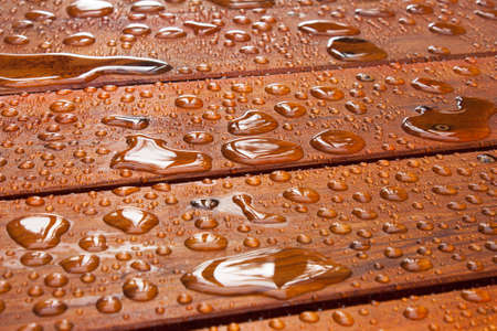 decks: A close up on a recently sealed cottage deck just after the summer rain   Water beads up in reflective pools as the sun begins to shine
