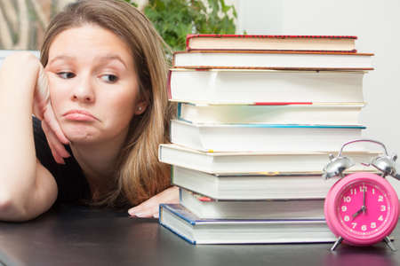 A young woman glances sideways at the large pile of books for exam study time.  Time ticks on reminding her of the limited time to finish the task.  Stock Photo