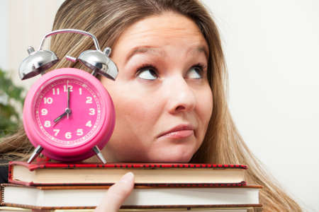 frowns: A young woman frowns and rolls her eyes upwards, wondering how she will be able to complete homework she has to finish Stock Photo