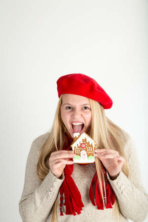 devour: A young woman about to enthusiastically devour a gingerbread cookie