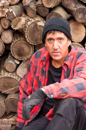 wood cutter: A middle aged man takes a break from splitting wood